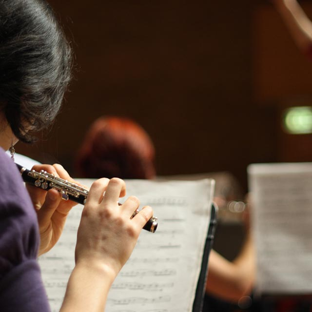 woman playing a piccolo in a performance of music